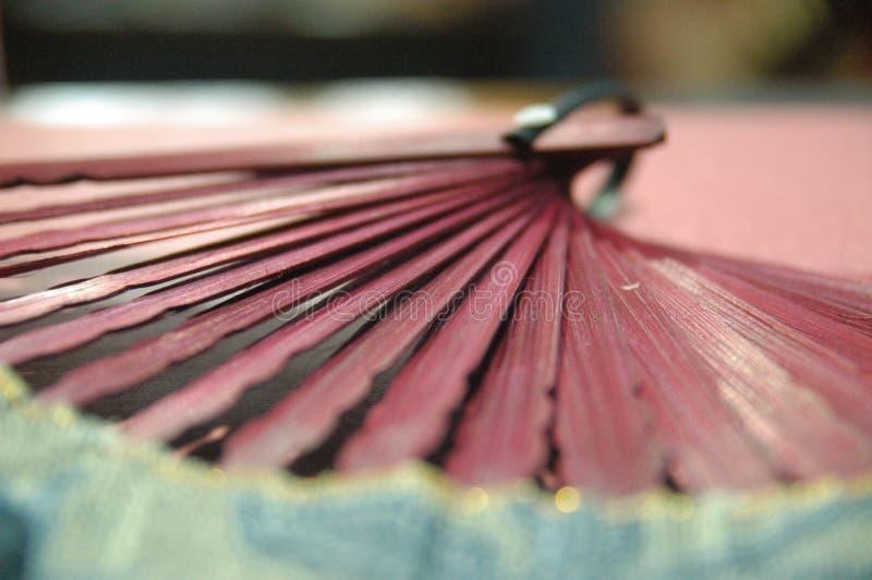 Hölzerner Abschluss des Frauenhandfans rote Farboben lizenzfreies stockbild