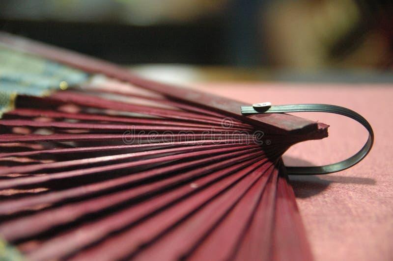 Hölzerner Abschluss des Frauenhandfans rote Farboben stockfotografie