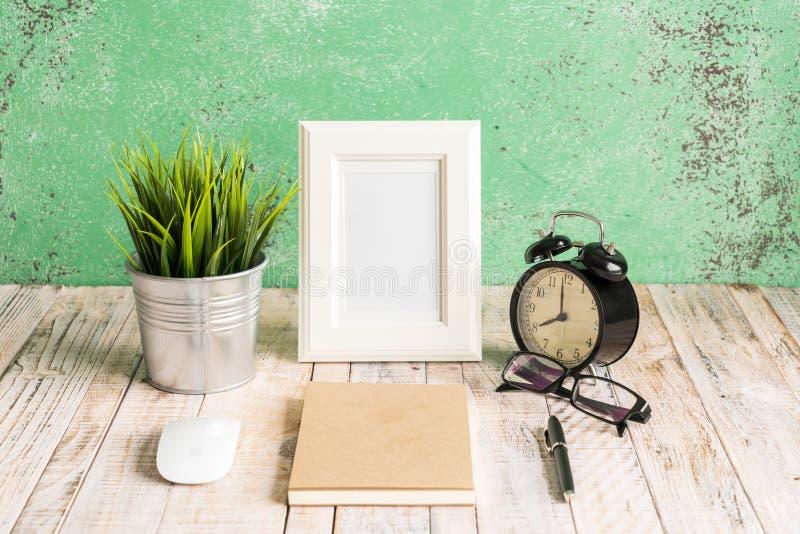 Hölzerner Arbeitsplatzdesktop mit Uhr; Anlagen; Gläser; Rahmen und stockfotos