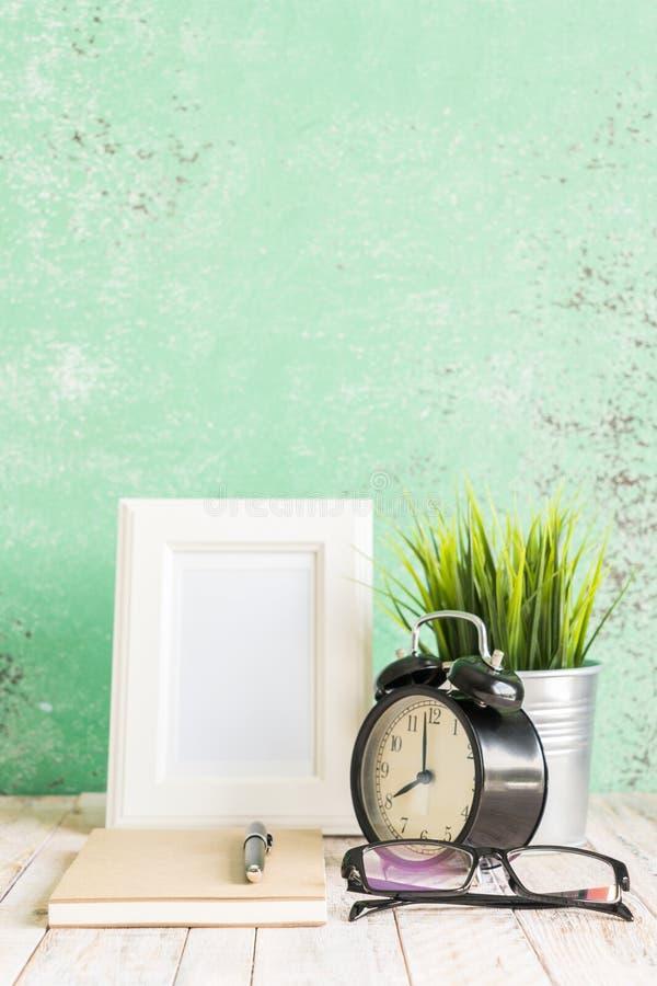 Hölzerner Arbeitsplatzdesktop mit Uhr; Anlagen; Gläser; Rahmen und stockbilder