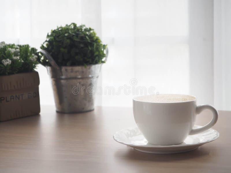 Hölzerner Bürotisch mit Schale des Lattekaffees und der schönen Blume stockfotos