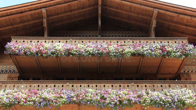 Hölzerner Balkon mit blühenden bunten Petunien lizenzfreie stockfotografie