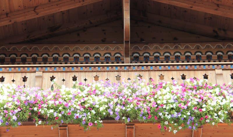Hölzerner Balkon mit blühenden bunten Petunien lizenzfreie stockfotos