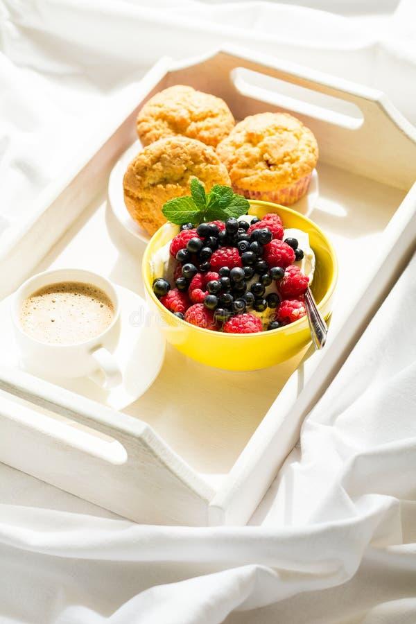 Hölzerner Behälter mit geschmackvollem Frühstück auf Bett Espresso, Bananenmuffins, Hüttenkäse mit Blaubeere und Himbeere lizenzfreie stockfotos