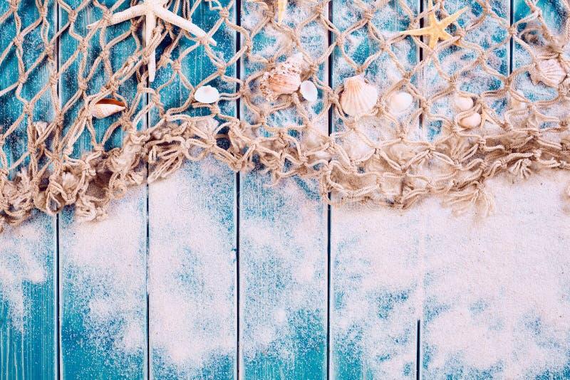 Hölzerner blauer Hintergrund mit Sand, Netz und Oberteilen lizenzfreie stockfotografie
