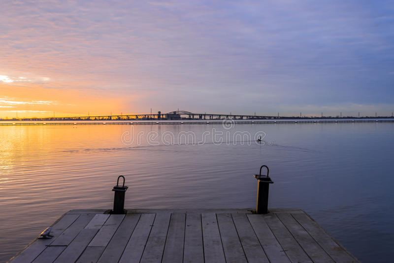 Hölzerner Bootspier, der heraus zu vibrierenden bunten Sonnenaufgang über tr führt stockfotos