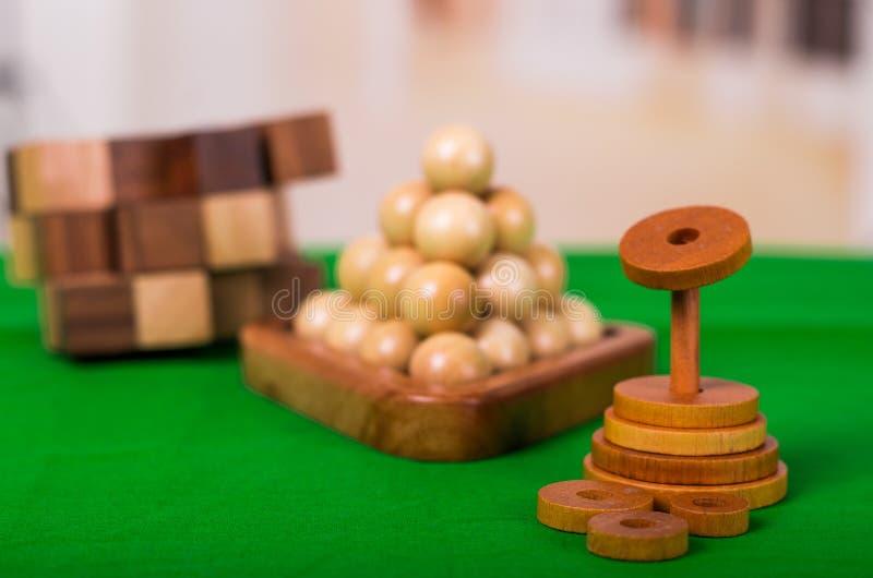 Hölzerner Brain Teaser oder hölzerne Puzzlespiele auf grünem Boden in unscharfem Hintergrund lizenzfreie stockfotografie