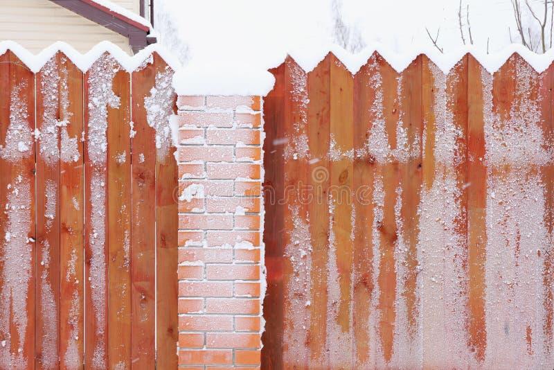 Hölzerner brauner Zaun mit Ziegelsteinsäule im Schnee und im ländlichen Li des Frosts lizenzfreies stockbild