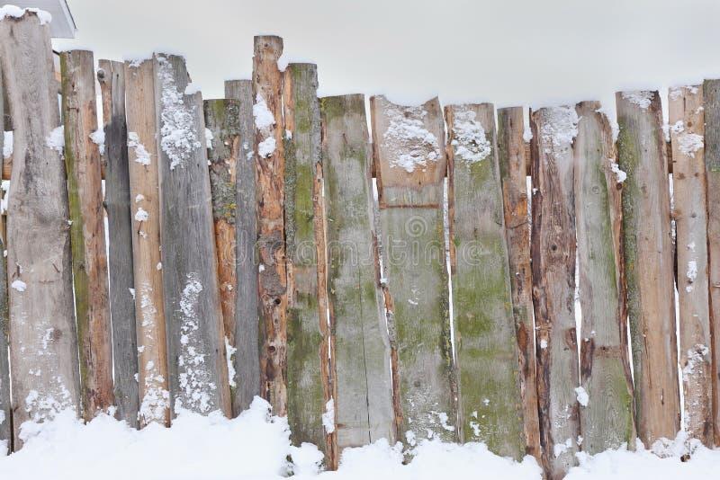 Hölzerner brauner Zaun von rauen Brettern im Schnee stockfotos