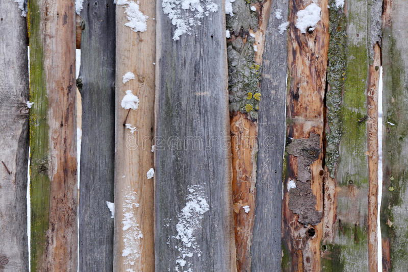 Hölzerner brauner Zaun von rauen Brettern im Schnee lizenzfreies stockfoto