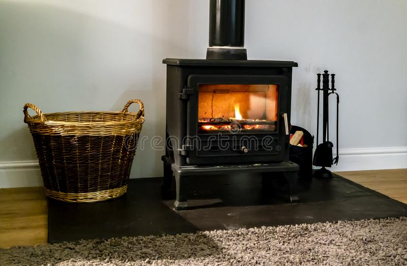 Hölzerner brennender Kamin mit Glastür stockbilder