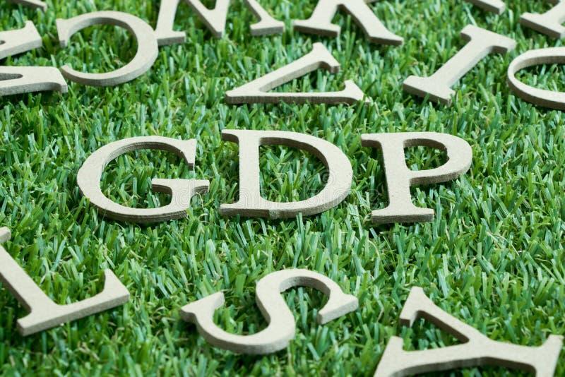 Hölzerner Buchstabe in Wort BIP Abkürzung von der guten Verteilungspraxis oder Bruttoinlandsprodukt auf künstlichem grünem Gras lizenzfreie stockfotografie