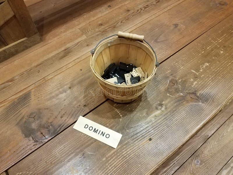 Hölzerner Eimer mit Dominos auf braunem Holzfußboden stockbilder