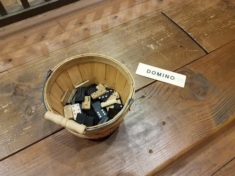 Hölzerner Eimer mit Dominos auf braunem Holzfußboden stockbild