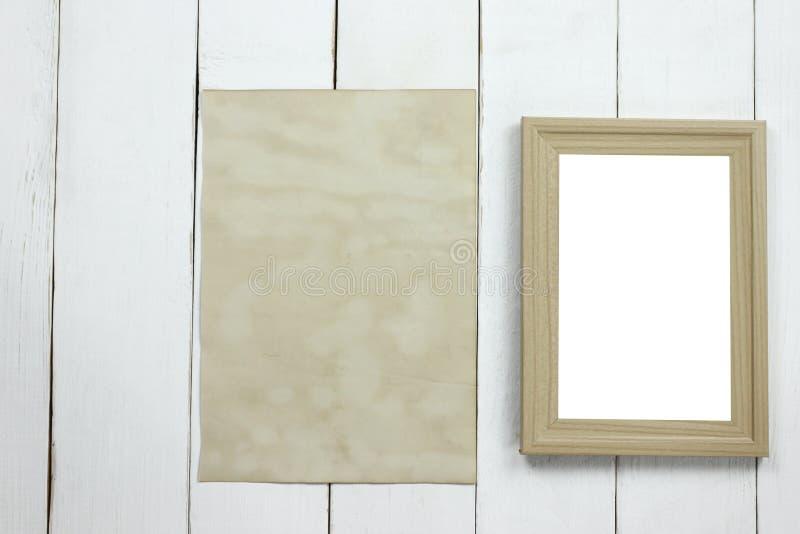 Hölzerner Fotorahmen und altes leeres Weinlesepapier auf weißem hölzernem f stockfotos
