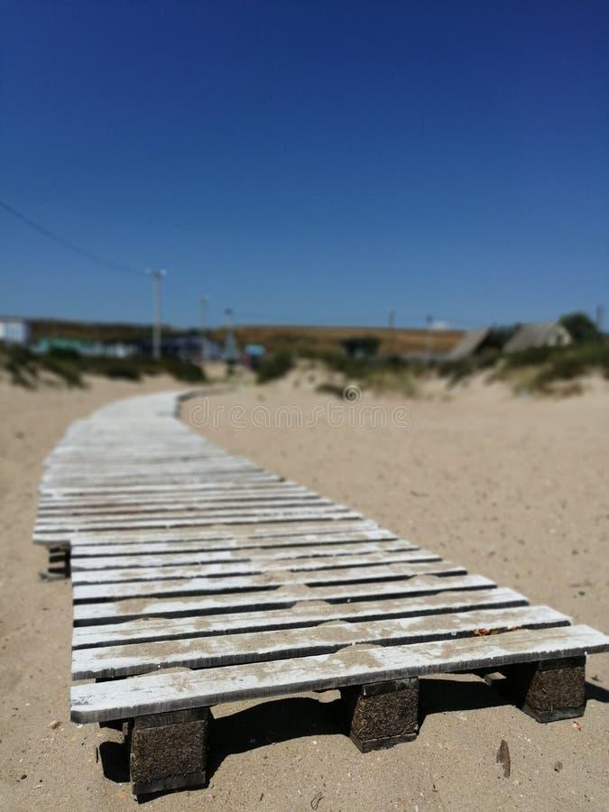 Hölzerner Fußweg auf dem Sand, der in Perspektive einsteigt lizenzfreie stockfotografie