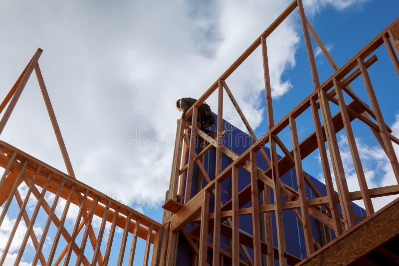 Hölzerner Gebäuderahmentischler bei der Arbeit mit hölzerner Dachkonstruktion stockbild