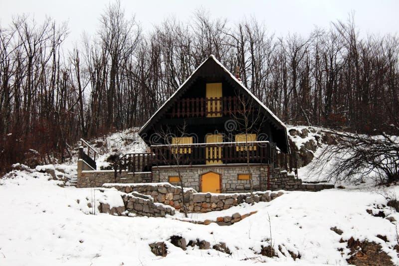 Hölzerner Gebirgsschnee bedeckte Häuschen mit Steingrundlage lizenzfreies stockbild