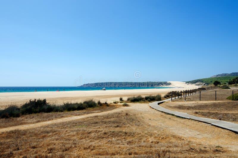 Hölzerner Gehweg zum schönen wilden Strand Playa de Bolonia auf der Atlantikküste von Tarifa stockfotos
