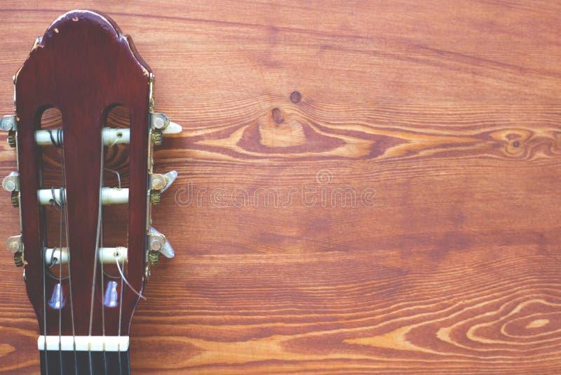 Hölzerner Hintergrund mit einem Fingerboard von der Gitarre, Draufsicht des flatlay Rahmens der Musik stockfotos