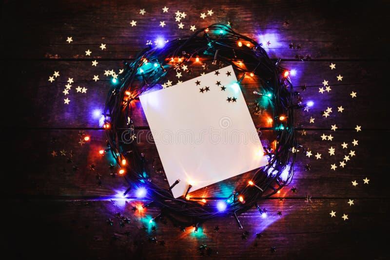Hölzerner Hintergrund mit farbigen Lichtern und Sternen In der Mitte gibt es Raum auf einem weißen Blatt für eine Feiertagsmittei lizenzfreie stockfotografie