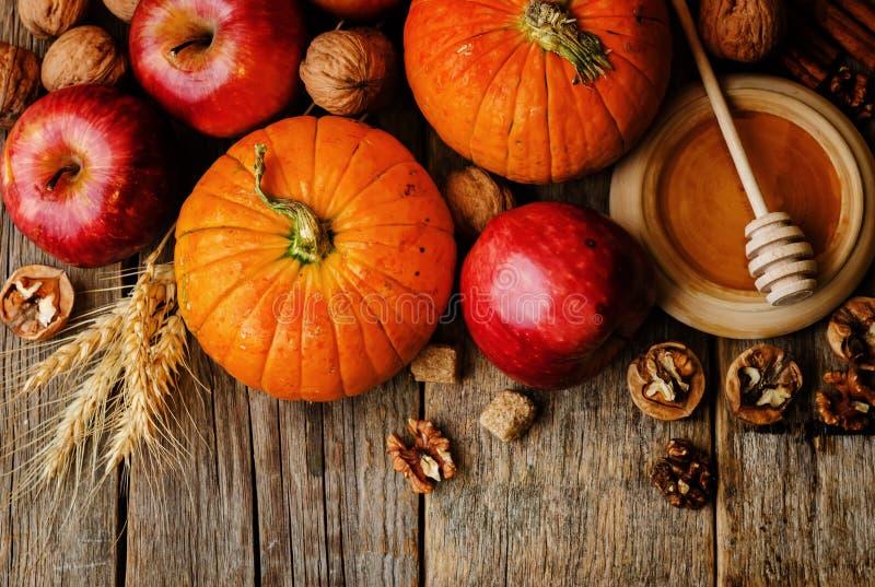 Hölzerner Hintergrund mit Kürbis, Äpfeln, Weizen, Honig und Nüssen lizenzfreies stockfoto
