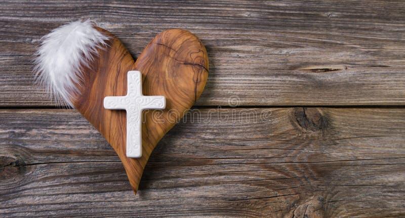 Hölzerner Hintergrund mit olivgrünem Herzen und weißes Kreuz für ein obitua lizenzfreies stockbild