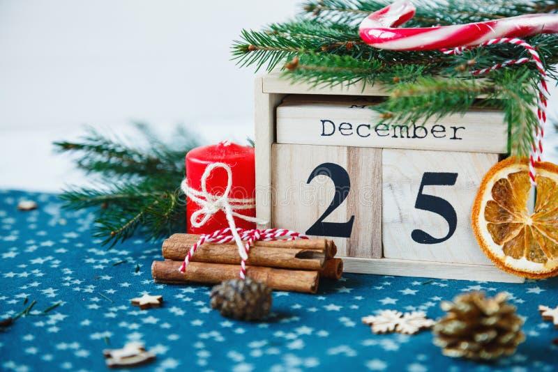 Hölzerner Kalender mit am 25. Dezember Datum in ihm auf grüner Platzmatte, Kerze, Tannenbaum, getrocknete Orangen, Kiefern Mutter stockfotos