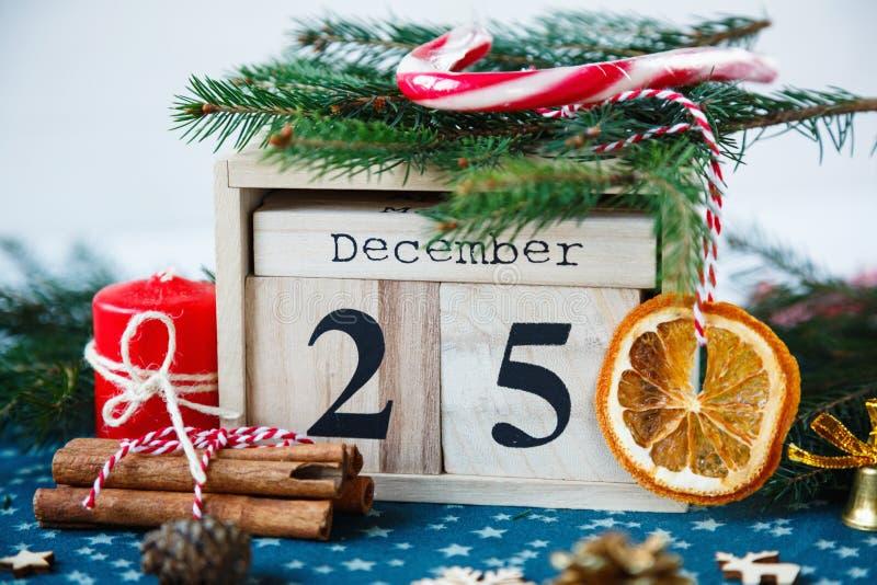 Hölzerner Kalender mit am 25. Dezember Datum in ihm auf grüner Platzmatte, Kerze, Tannenbaum, getrocknete Orangen, Kiefern Mutter stockbild