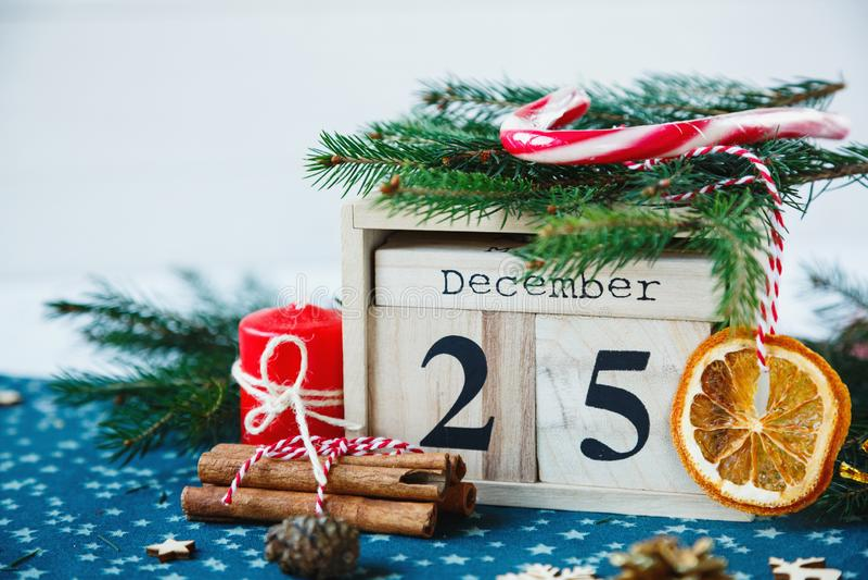 Hölzerner Kalender mit am 25. Dezember Datum in ihm auf grüner Platzmatte, Kerze, Tannenbaum, getrocknete Orangen, Kiefern Mutter lizenzfreie stockfotografie