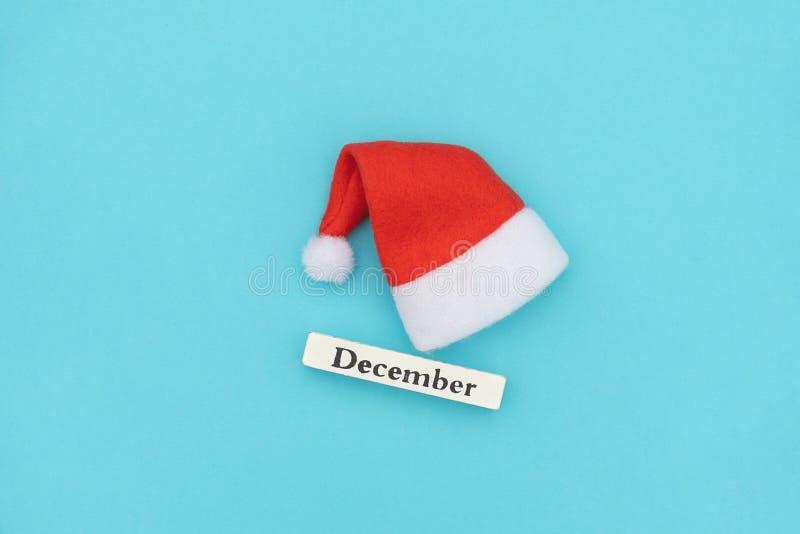 Hölzerner Kalenderwintermonat Dezember und Sankt-Hut auf blauem Papierhintergrund Konzept-Weihnachten oder neues Jahr Kreative Dr stockbild