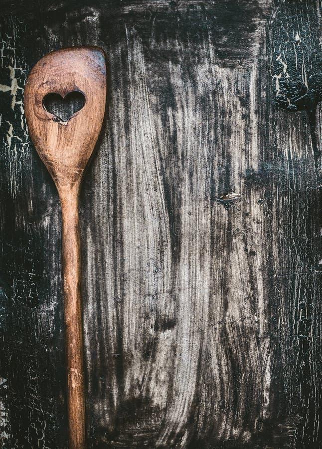 Hölzerner kochender Löffel mit Herzen auf dunklem rustikalem Hintergrund, Draufsicht Lebensmittelhintergrund für Rezepte lizenzfreie stockbilder