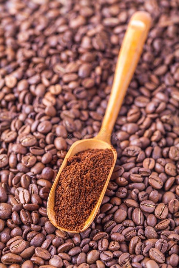 hölzerner Löffel mit Bohnenhintergrund des gemahlenen Kaffees lizenzfreies stockbild