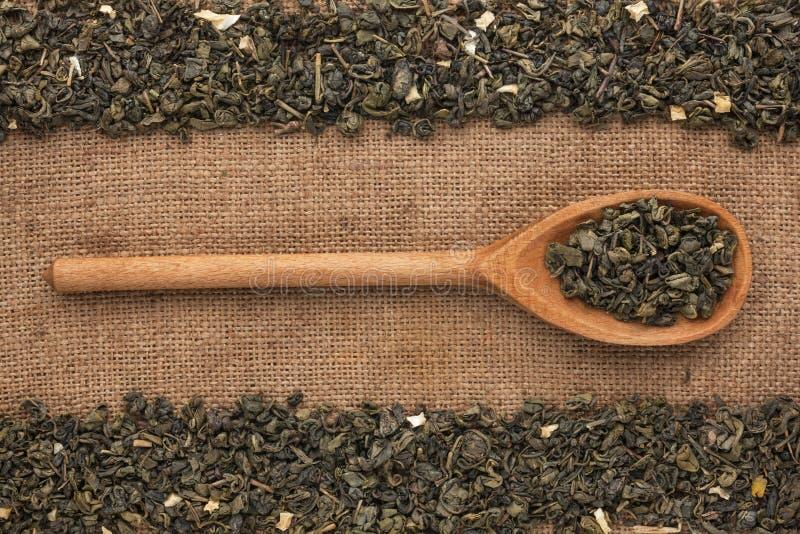 Hölzerner Löffel mit grünem Tee liegt auf Sackleinen stockfotografie