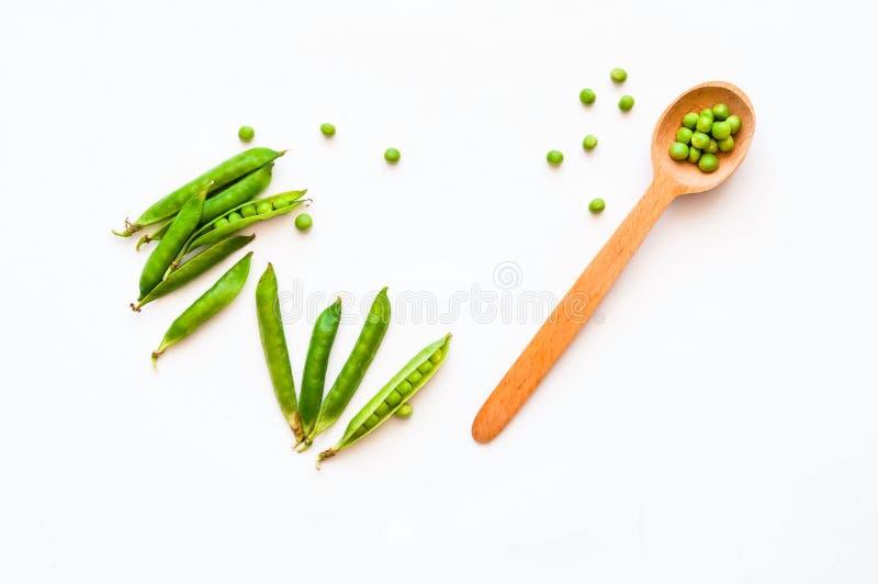 Hölzerner Löffel mit grünen Erbsen auf lokalisiertem weißem Hintergrund Das Konzept von Bioprodukten für das Kochen stockbilder