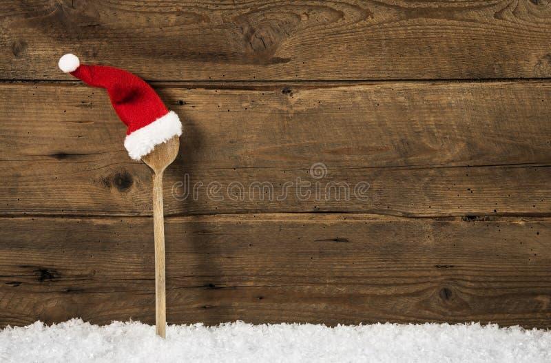 Hölzerner Löffel mit Sankt-Hut: rustikaler Weihnachtshintergrund lizenzfreies stockfoto