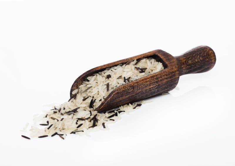 Hölzerner Löffel von rohem organischem Basmatilangkörnigem und Wildreise auf weißem Hintergrund Gesunde Nahrung lizenzfreies stockfoto