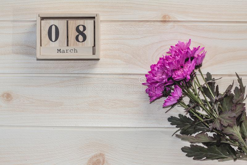 Hölzerner am 8. März Kalender, nahe bei purpurroten Blumen auf Holztisch stockfotos