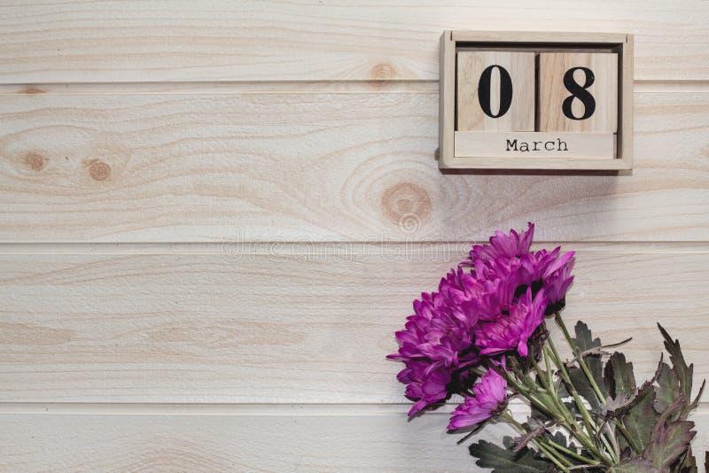 Hölzerner am 8. März Kalender, nahe bei purpurroten Blumen auf Holztisch stockfoto