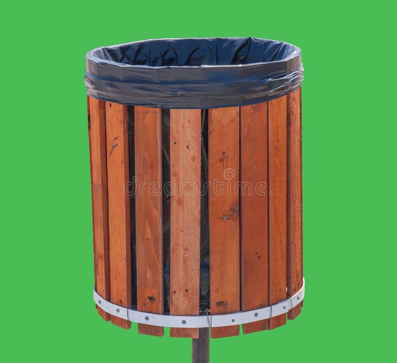 Hölzerner Mülleimer für den Abfall lokalisiert auf grünem Hintergrund lizenzfreie stockbilder