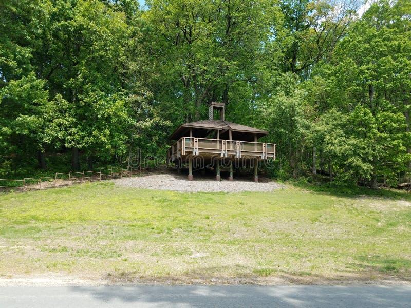 Hölzerner Picknickpavillon Browns auf Hügel mit grünem Gras und Bäumen stockfotos
