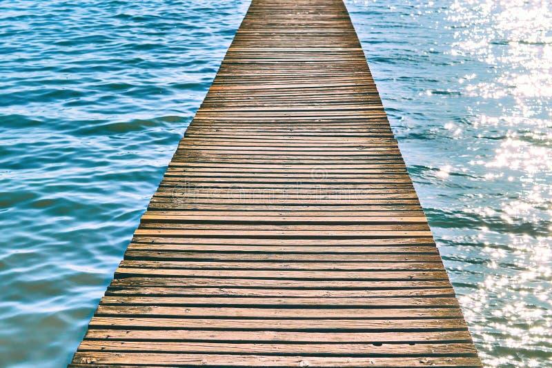 Hölzerner Pier über Wasser mit Wellen an einem sonnigen Sommertag lizenzfreie stockbilder
