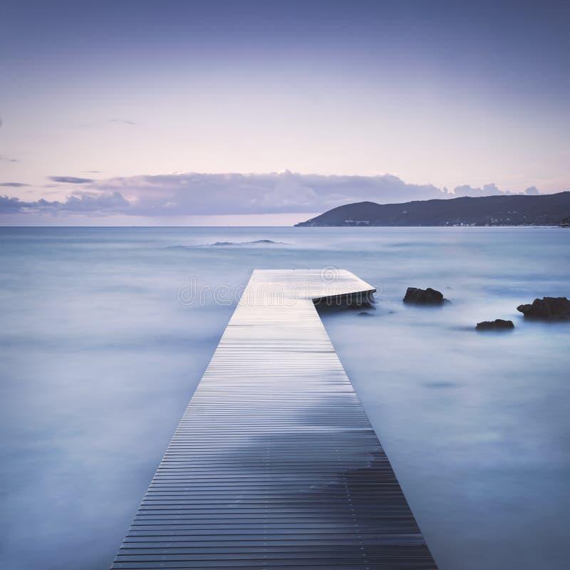 Hölzerner Pier, Felsen und Meer auf nebelhaftem Sonnenuntergang lizenzfreies stockbild