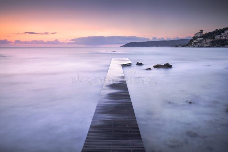 Hölzerner Pier, Felsen und Meer Castiglioncello-Bucht auf Sonnenuntergang toskaneres lizenzfreie stockfotografie