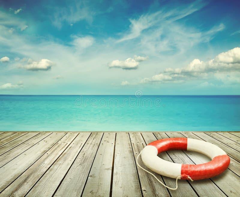 Hölzerner Pier mit Ozean und Schwimmweste lizenzfreie stockbilder