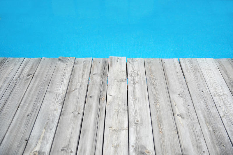 Hölzerner Plankenpier gegen blaues Wasser lizenzfreie stockfotografie