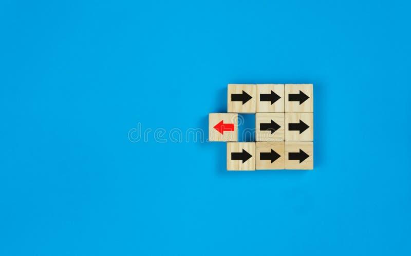 Hölzerner quadratischer Block, den das rote Pfeilsymbol zur entgegengesetzten Richtung des schwarzen Pfeilsymbols sich dreht lizenzfreies stockfoto