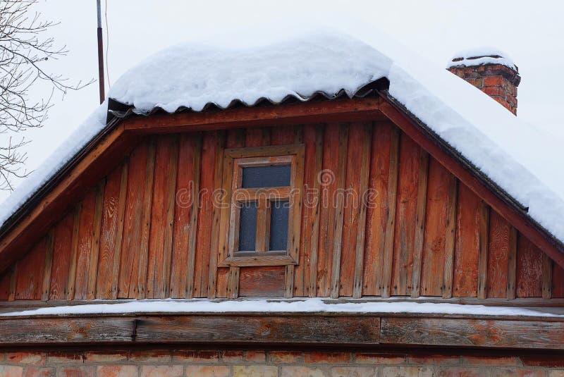 Hölzerner rustikaler Dachboden Browns mit Fenster unter weißem Schnee lizenzfreie stockfotografie