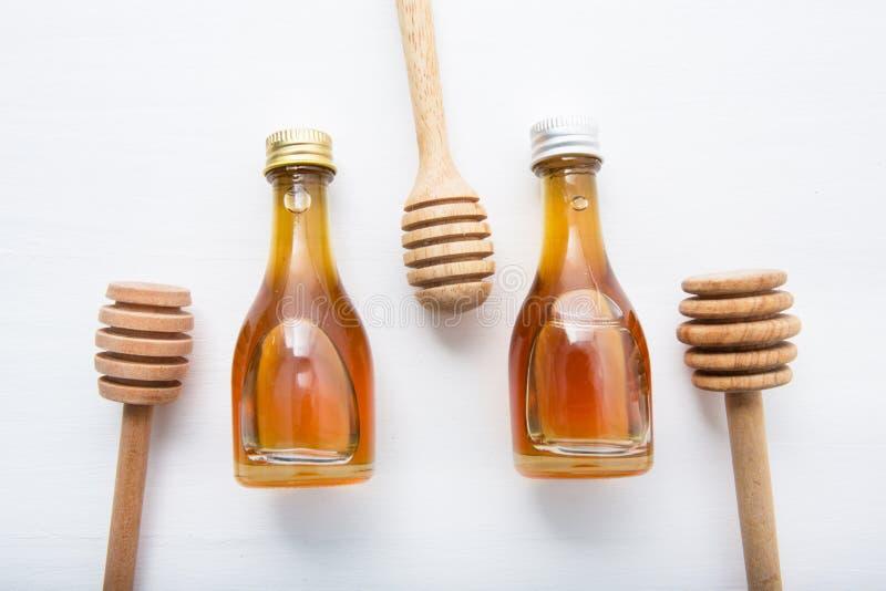 Hölzerner Schöpflöffel und wenig Honigflasche auf weißem hölzernem Hintergrund stockbilder