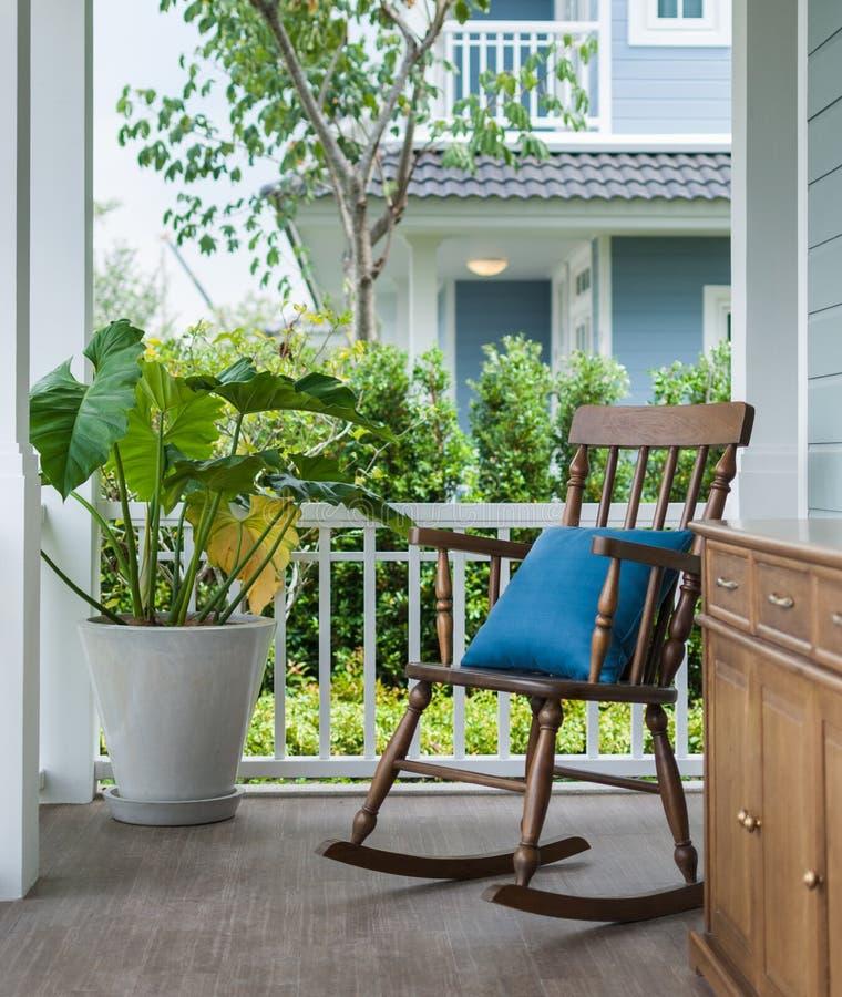 Hölzerner Schaukelstuhl auf Eingangsterrasse mit Kissen lizenzfreies stockbild